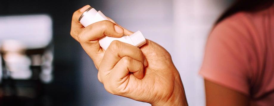 Asthma inhaler in a woman's hand