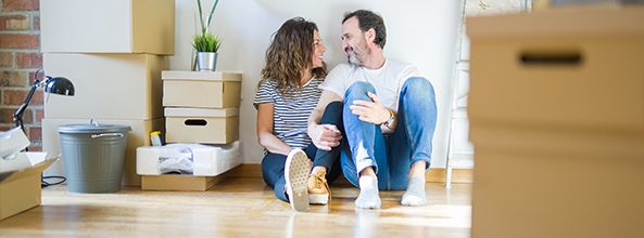 Couple sitting on the floor of their new home with boxes around them